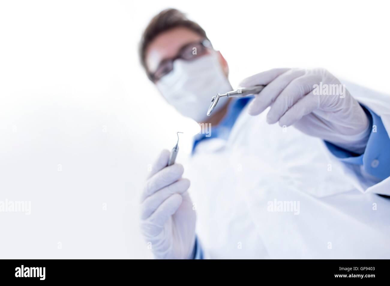 MODEL RELEASED. Dentist holding angled mirror. - Stock Image