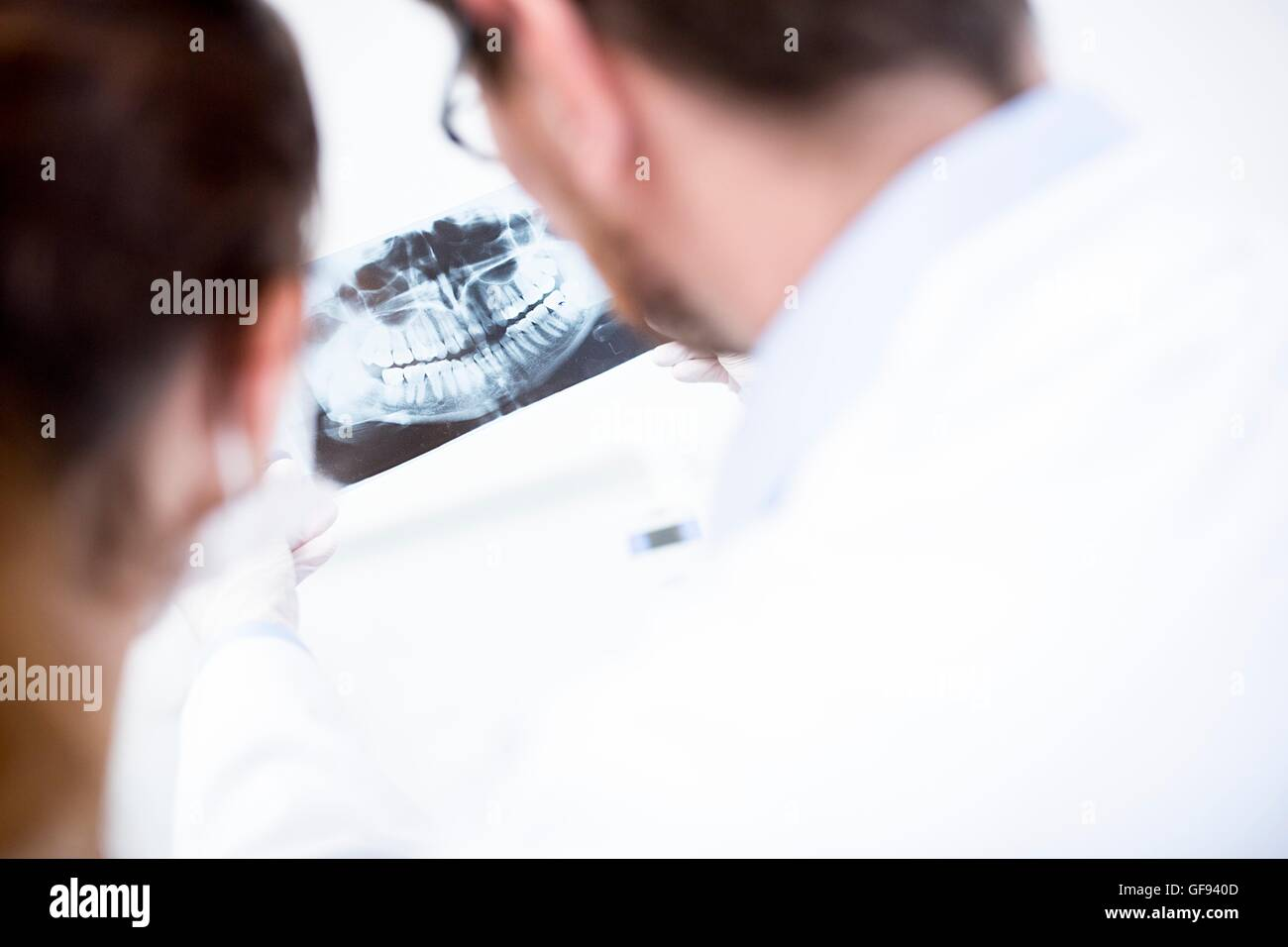 MODEL RELEASED. Dentist and dental assistant looking at x-ray image. - Stock Image