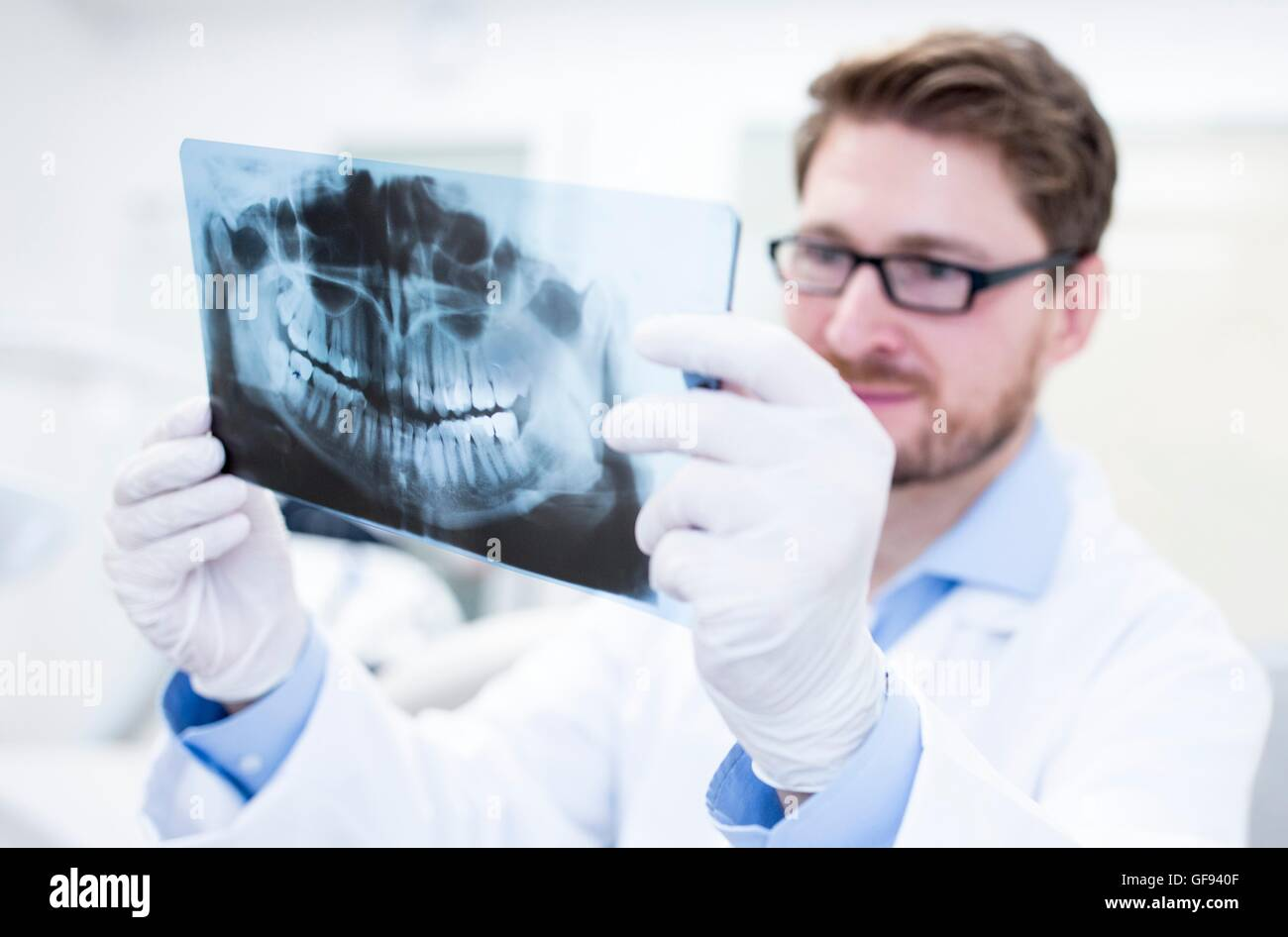 MODEL RELEASED. Dentist looking at x-ray image with dental assistance in background. - Stock Image