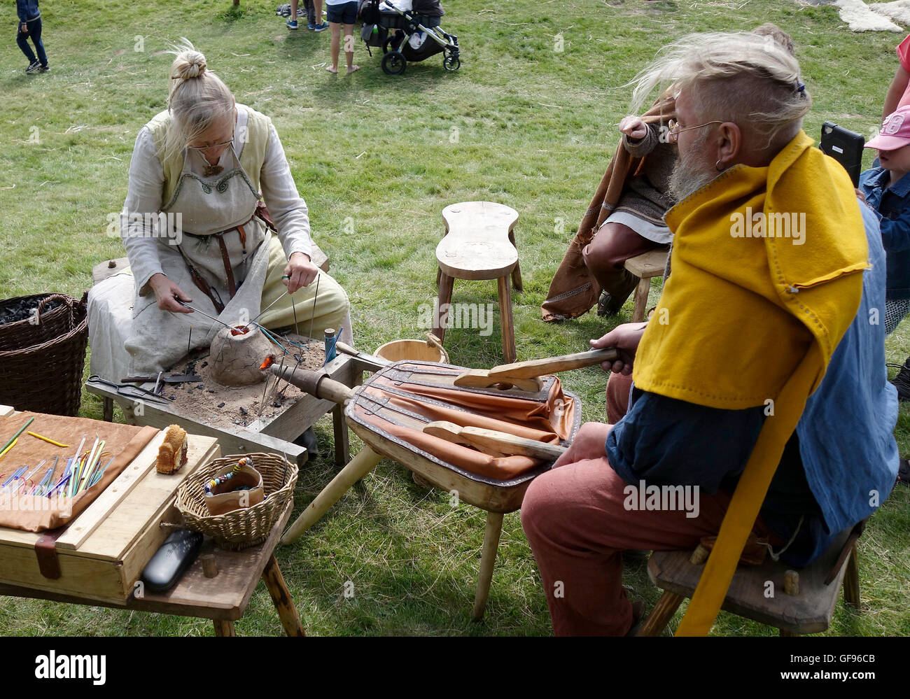 Elderly couple shows the early medieval glass pearl production by help of small portable clay furnace, Kungsbacka, - Stock Image