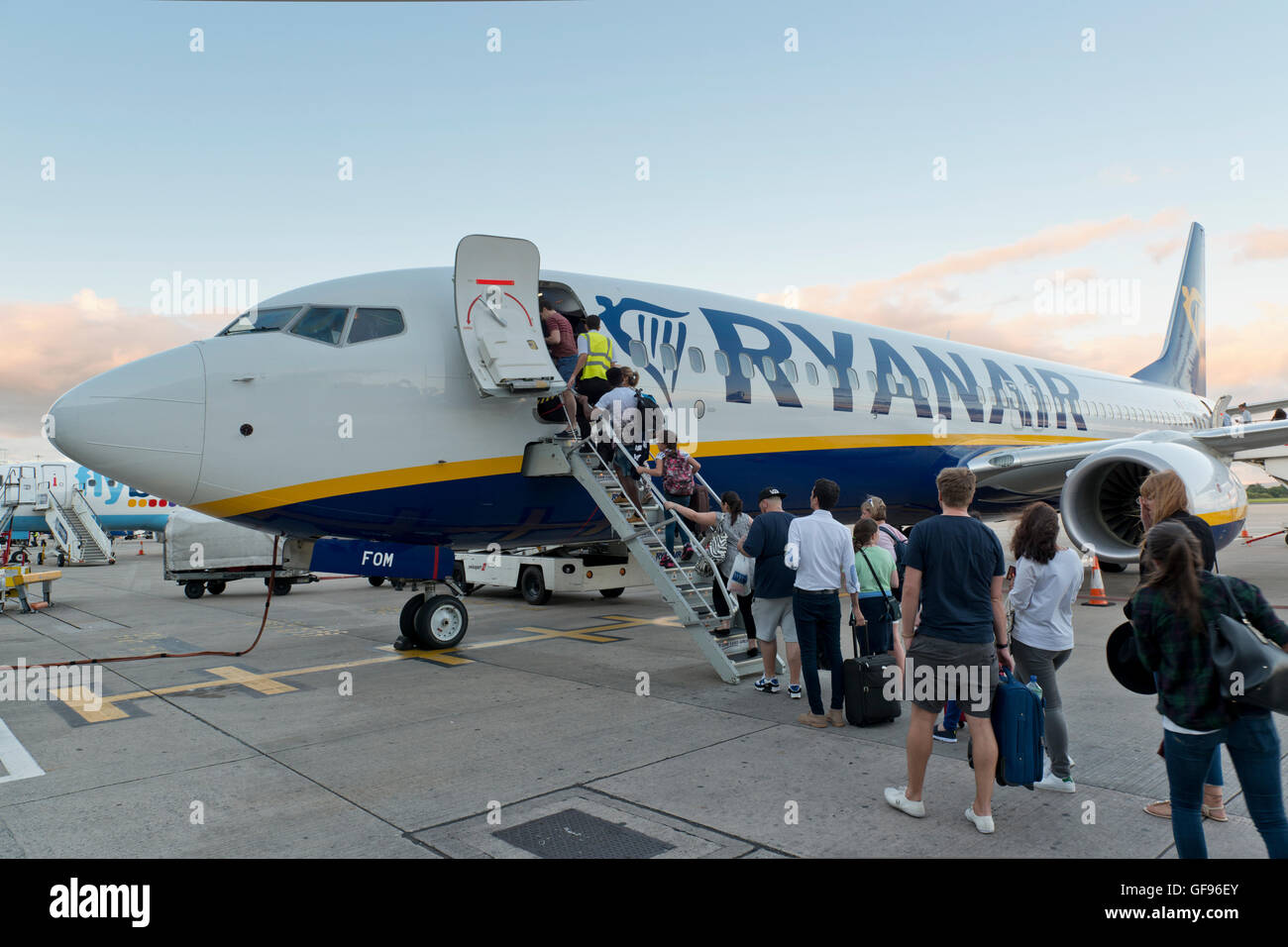Passengers board a Ryanair Boeing 737-800 aircraft on the apron of Manchester Airport (Editorial use only). - Stock Image