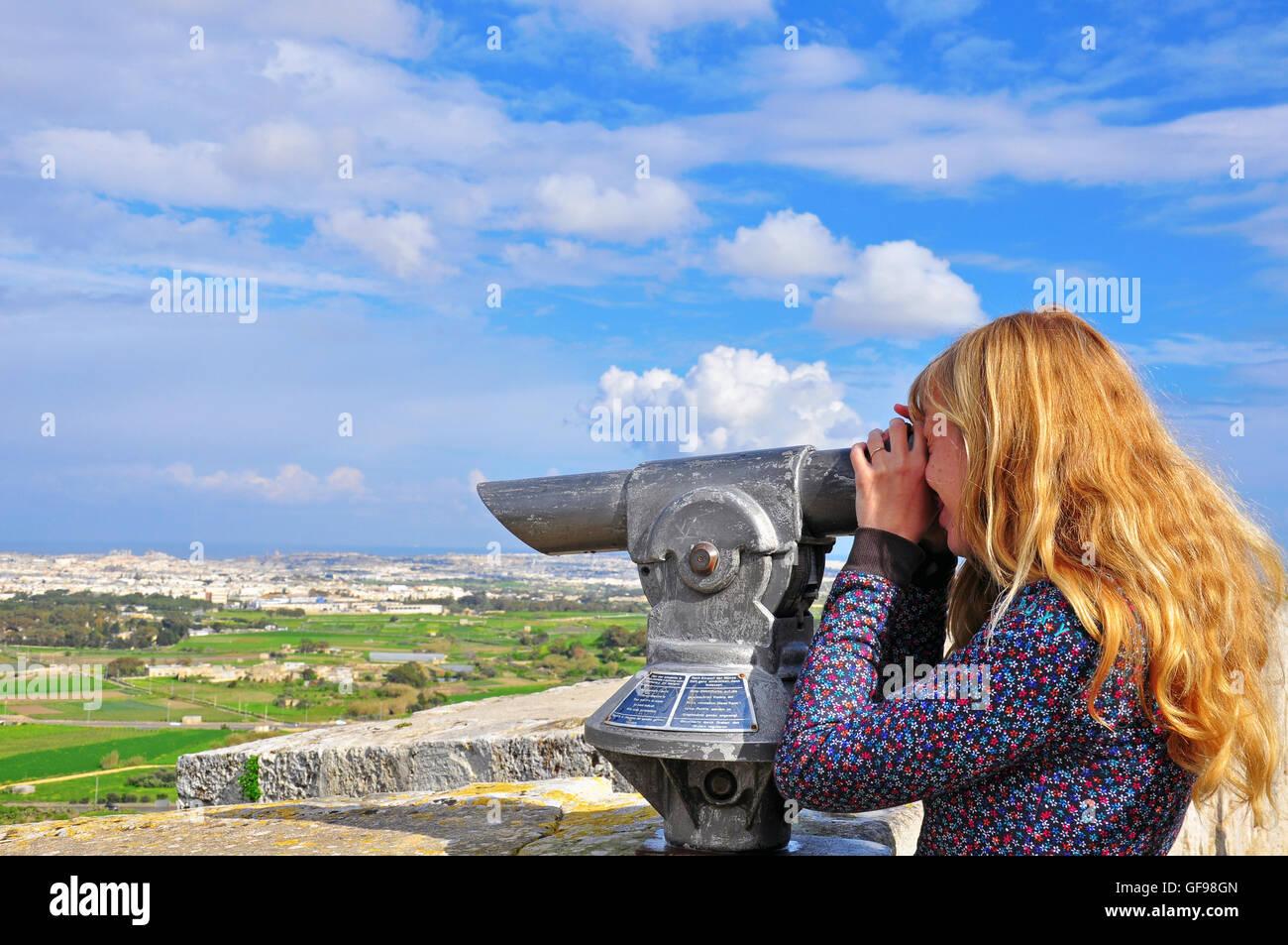 Blondy long-hair girl looking in telescope. Maltese Islands - Stock Image