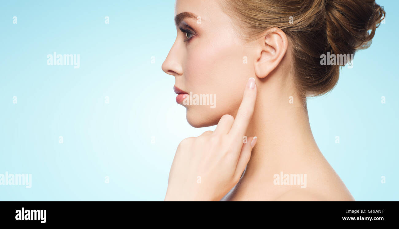 beautiful woman pointing finger to her ear - Stock Image