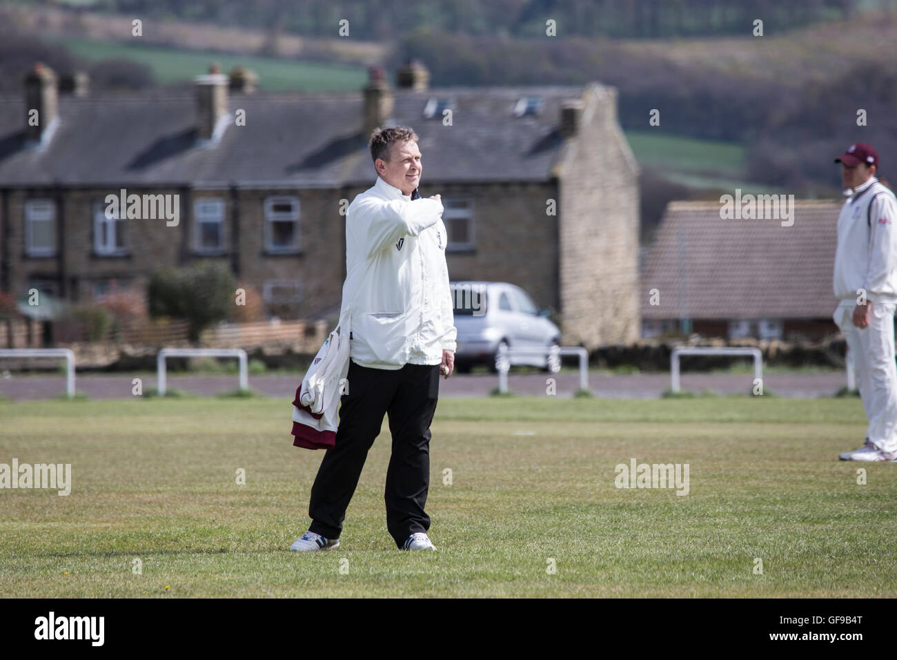 Cricket umpire signalling to the scorers during a village cricket game in England - Stock Image