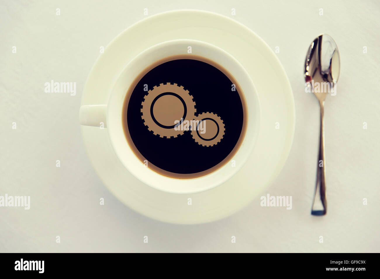 cup of coffee with cogwheel symbol and spoon - Stock Image