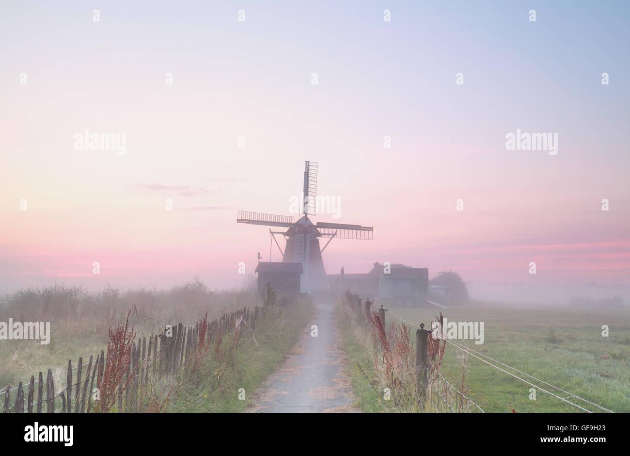 Dutch windmill in dense morning fog, Holland - Stock Image