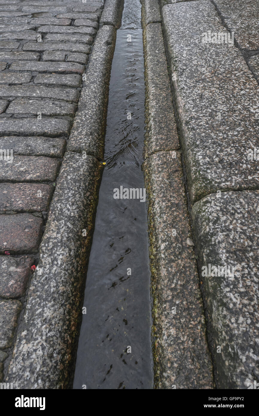Street drainage / gutter in Truro, Cornwall. Visual metaphor for 'money down the drain' and water waste - Stock Image