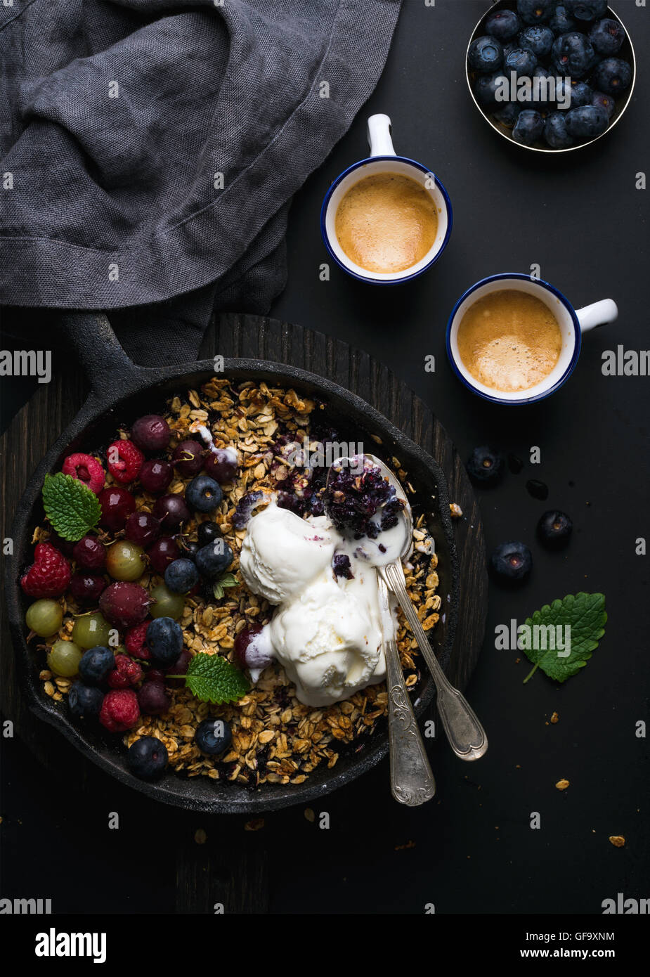 Healthy breakfast. Oat granola crumble with fresh berries, seeds and ice-cream in iron skillet pan on dark wooden - Stock Image