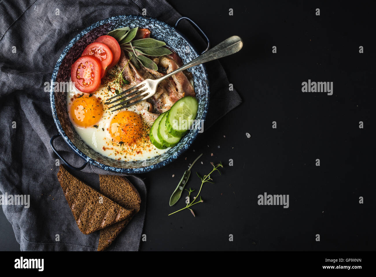 Breakfast set. Pan of fried eggs with bacon, fresh tomato, cucumber, sage and bread on dark serving board over black Stock Photo