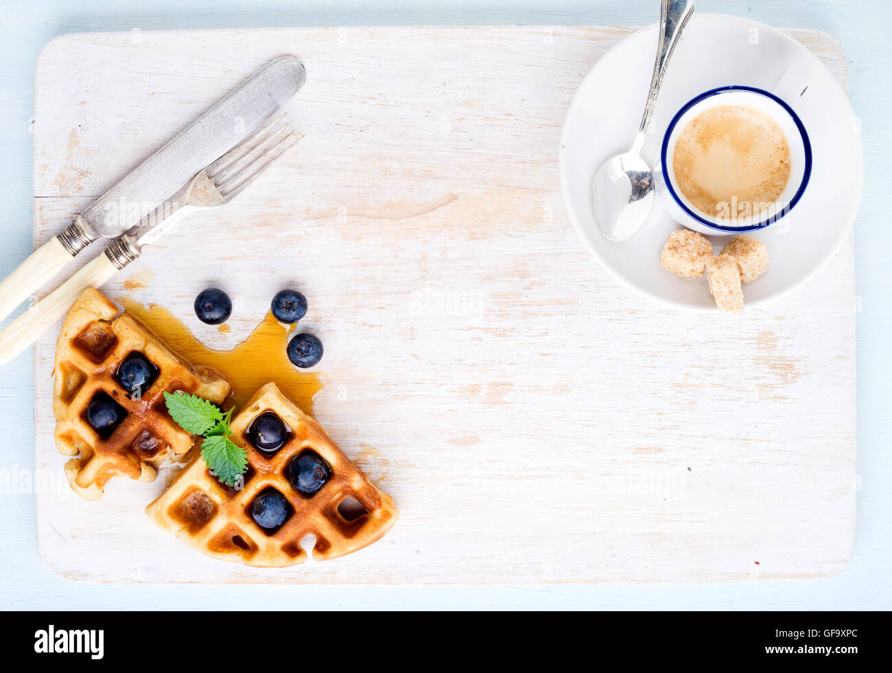 Espresso coffee cup, soft belgian waffles with fresh blueberries and marple syrup on white painted wooden board - Stock Image