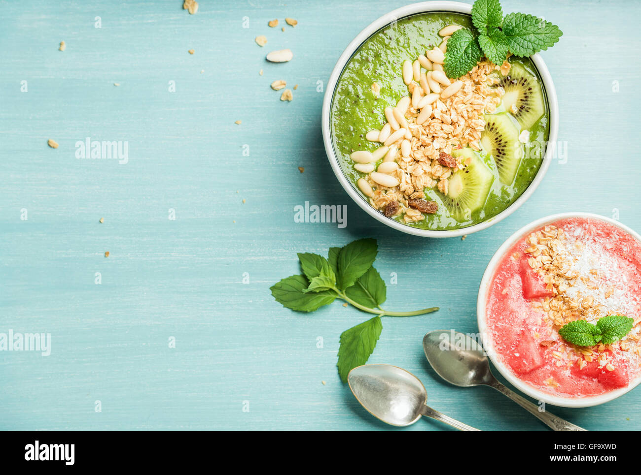 Healthy summer breakfast concept. Colorful fruit smoothie bowls on turquoise blue background - Stock Image