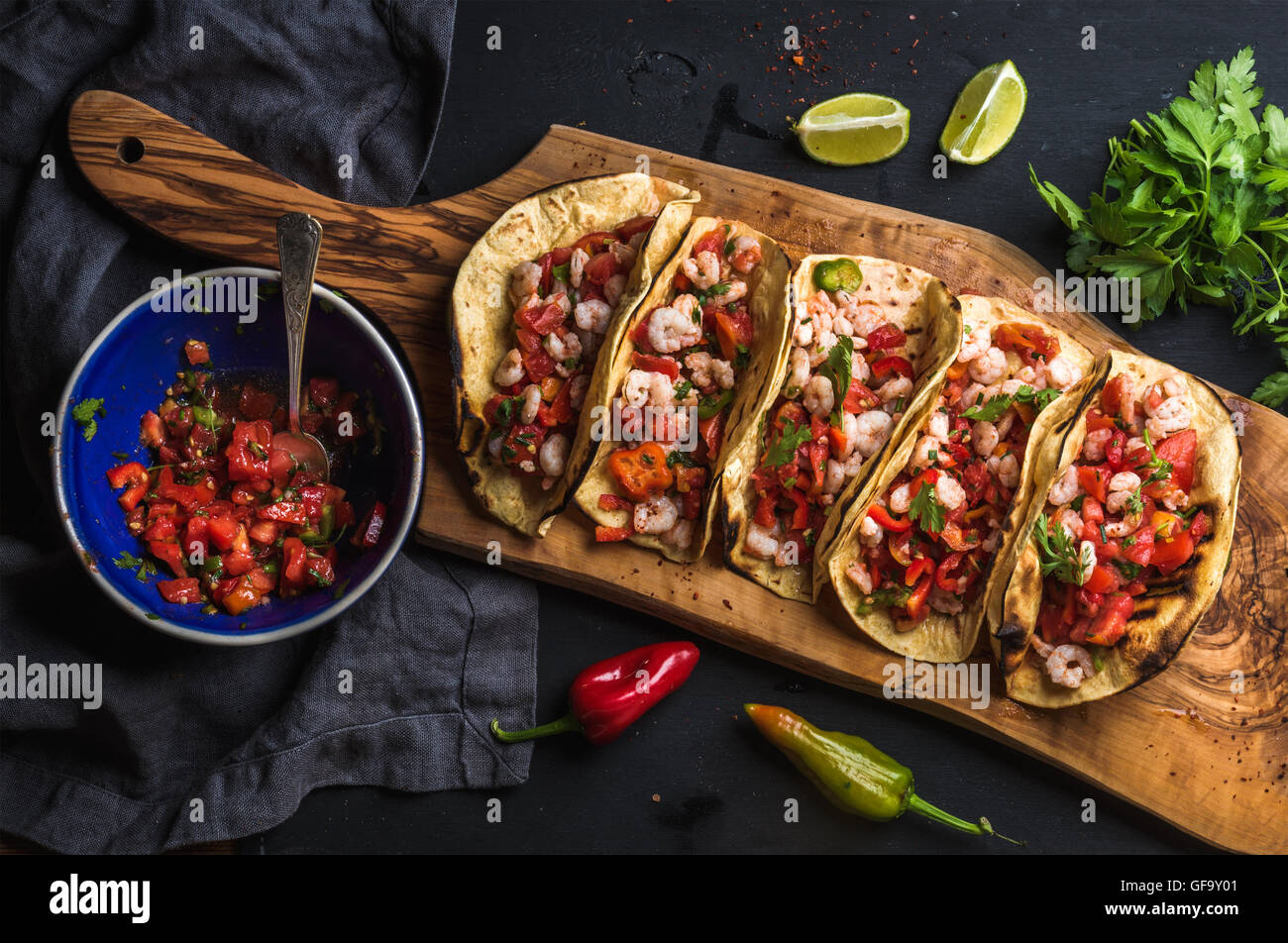 Shrimp tacos with homemade salsa, limes and parsley - Stock Image