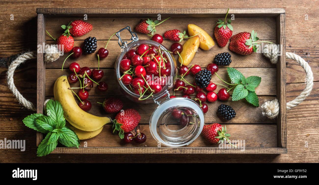 Healthy summer fruit variety. Sweet cherries, strawberries, blackberries, peaches, bananas and mint leaves - Stock Image