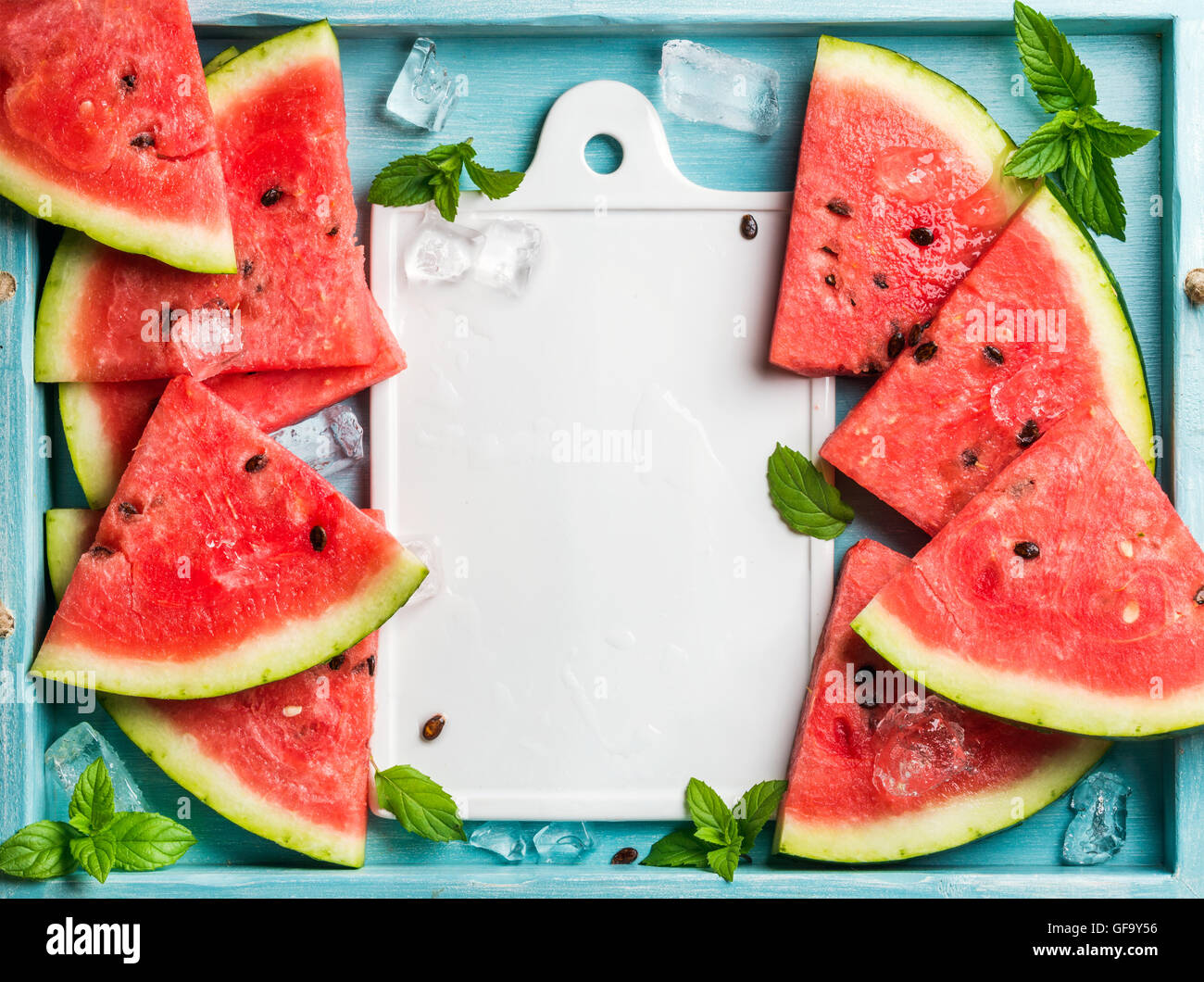 Watermelon slices with ice cubes and mint leaves on blue wooden background, white ceramic board in center. Top view, - Stock Image