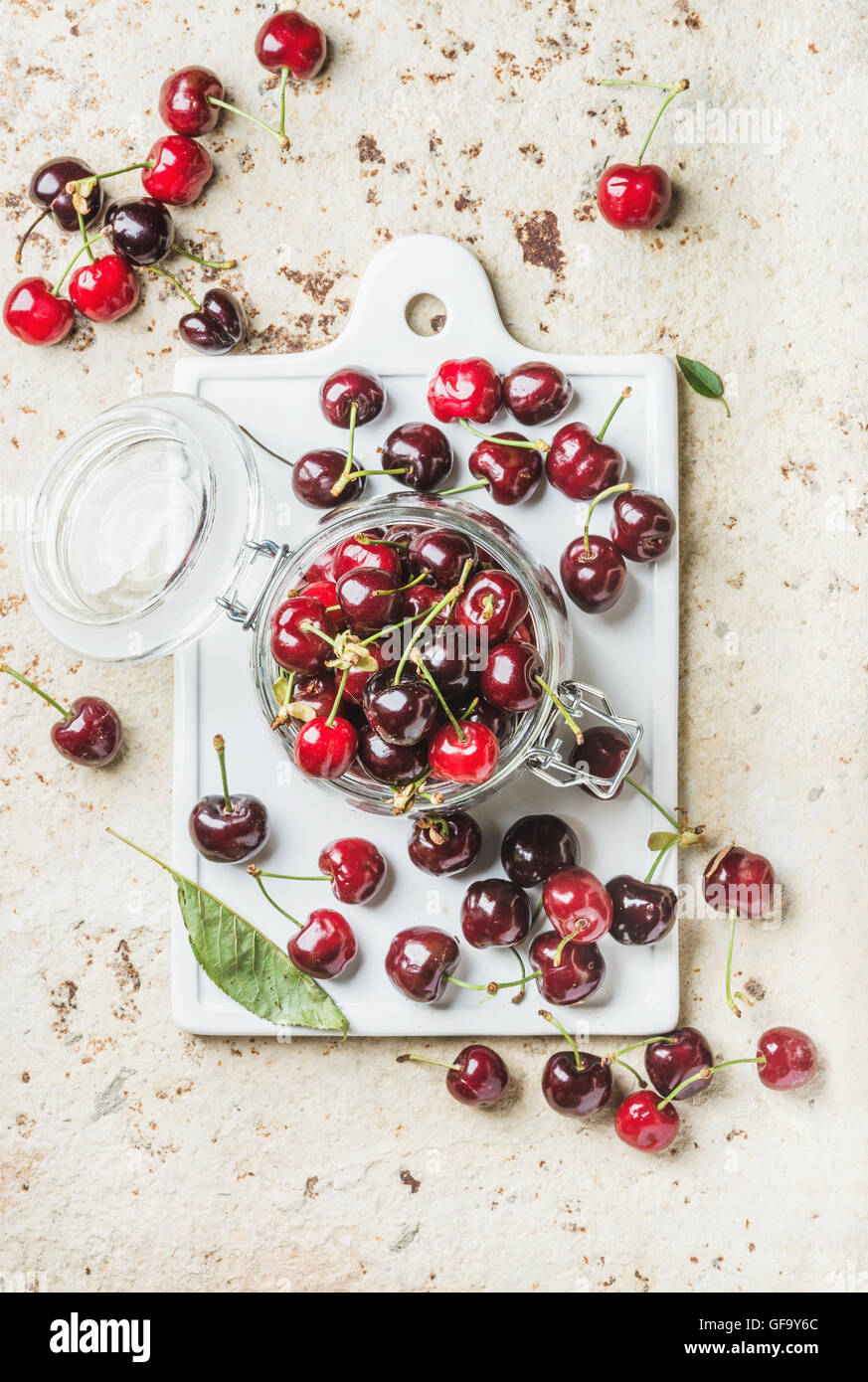 Sweet cherry in glass jar on white board over concrete background - Stock Image