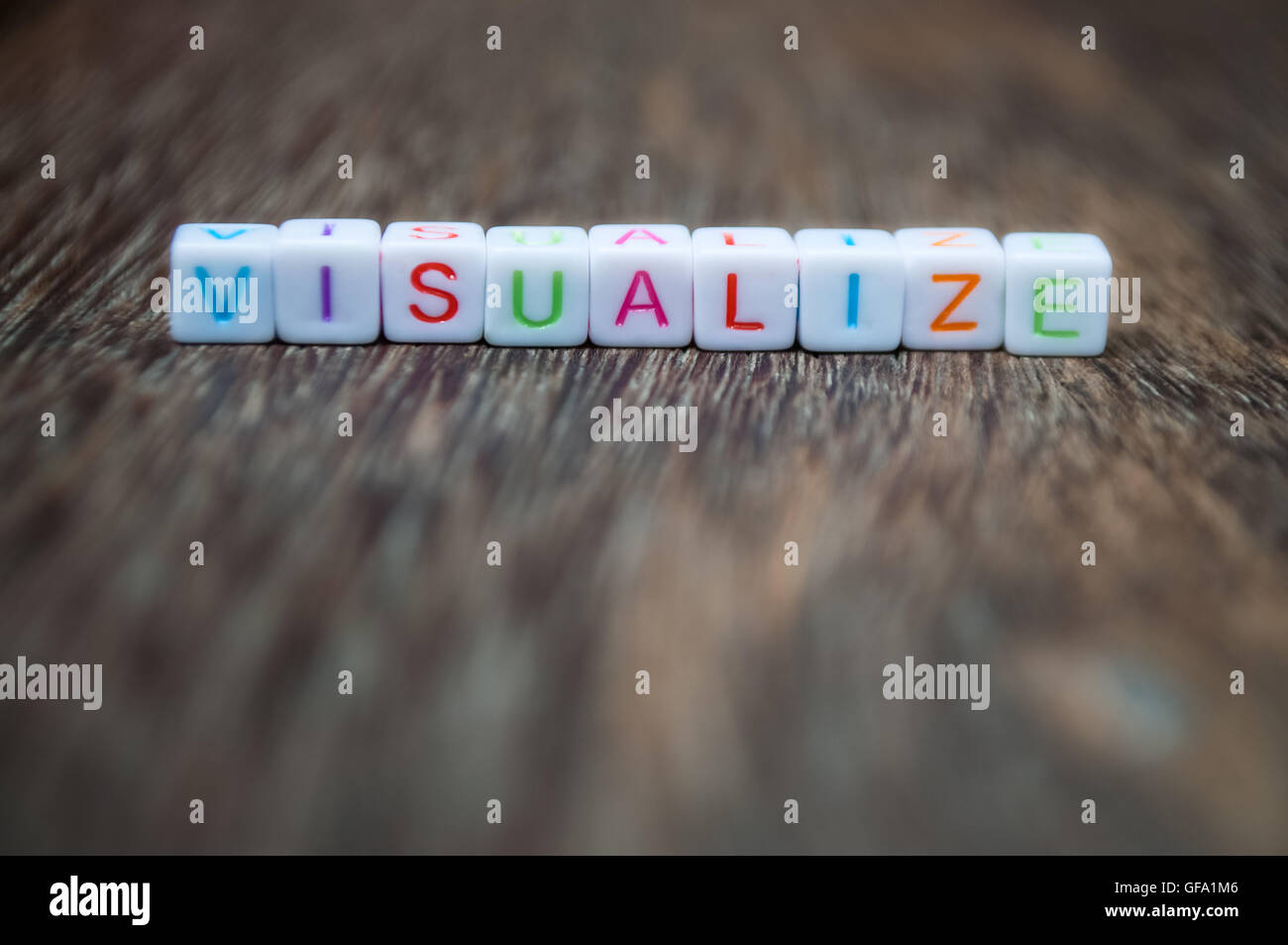 visualize word arranged from character cubes on wood table top. closeup. narrow depth of field. - Stock Image