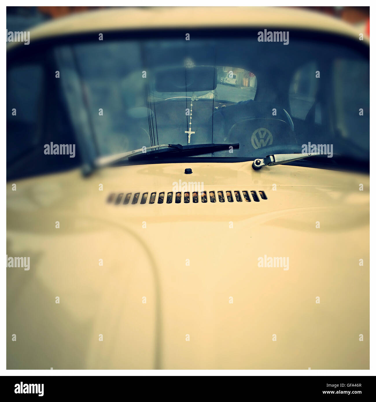 front of a yellow VW beetle - Stock Image