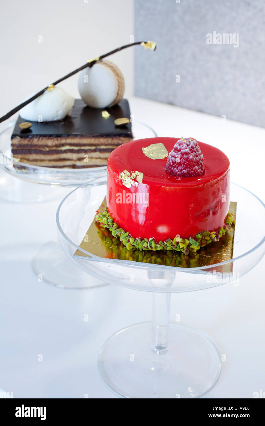 colorful jelly little cake raspberry flavor and tiramisu cake behind - Stock Image