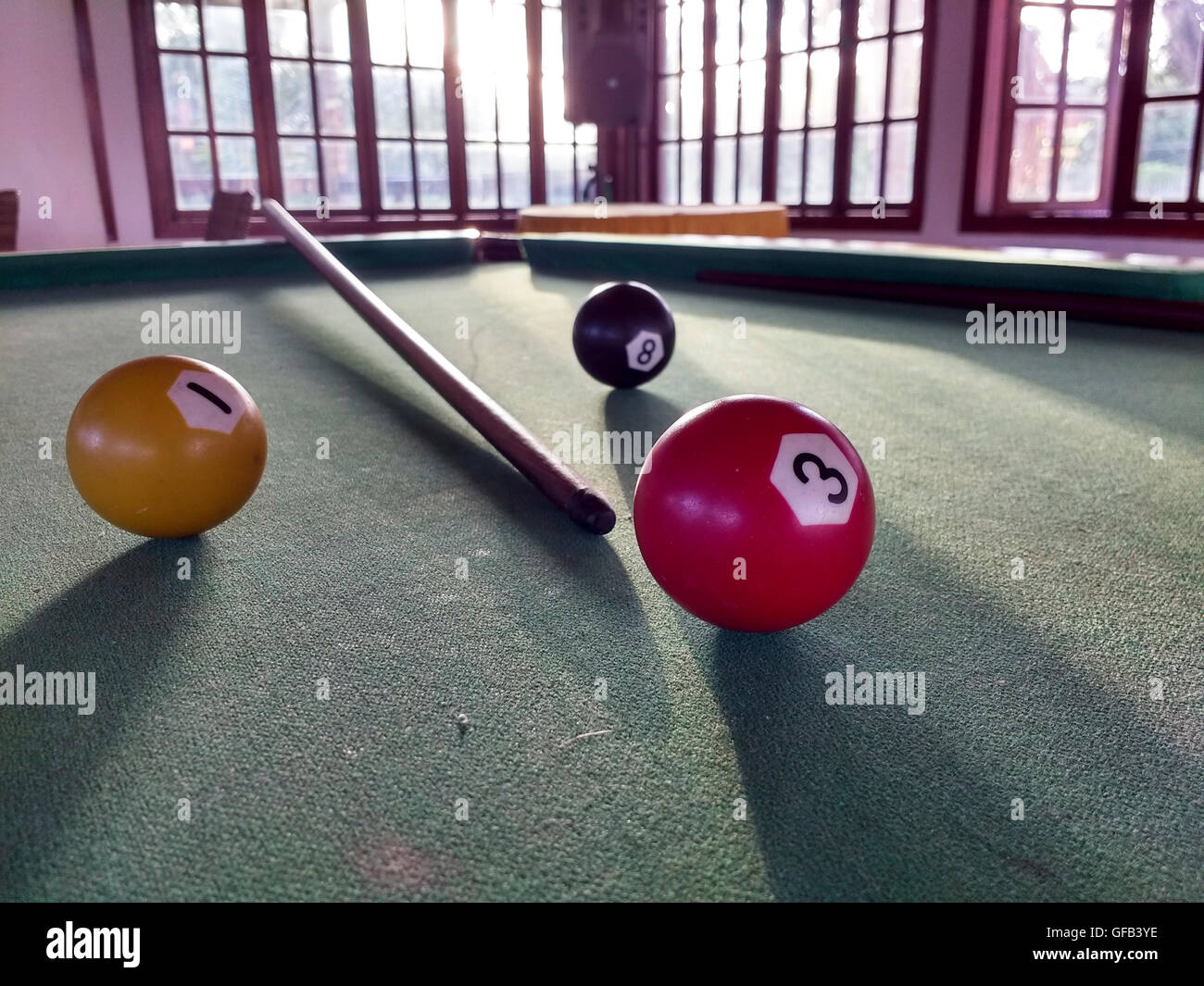 billiard table with windows in the background Stock Photo