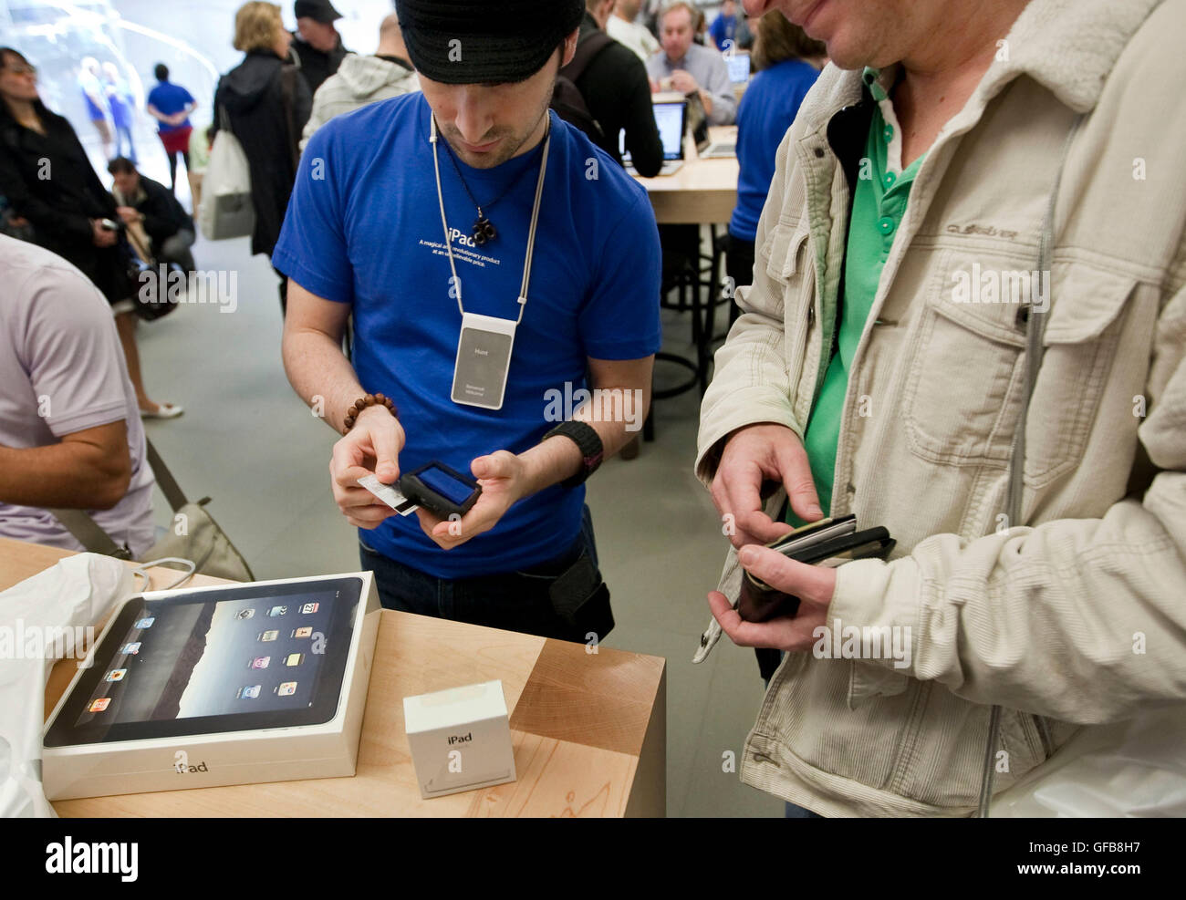 An Apple Store Employee L Blue Shirt Swipes A Credit Card On His IPhone To Charge Customer R For New IPad Announ