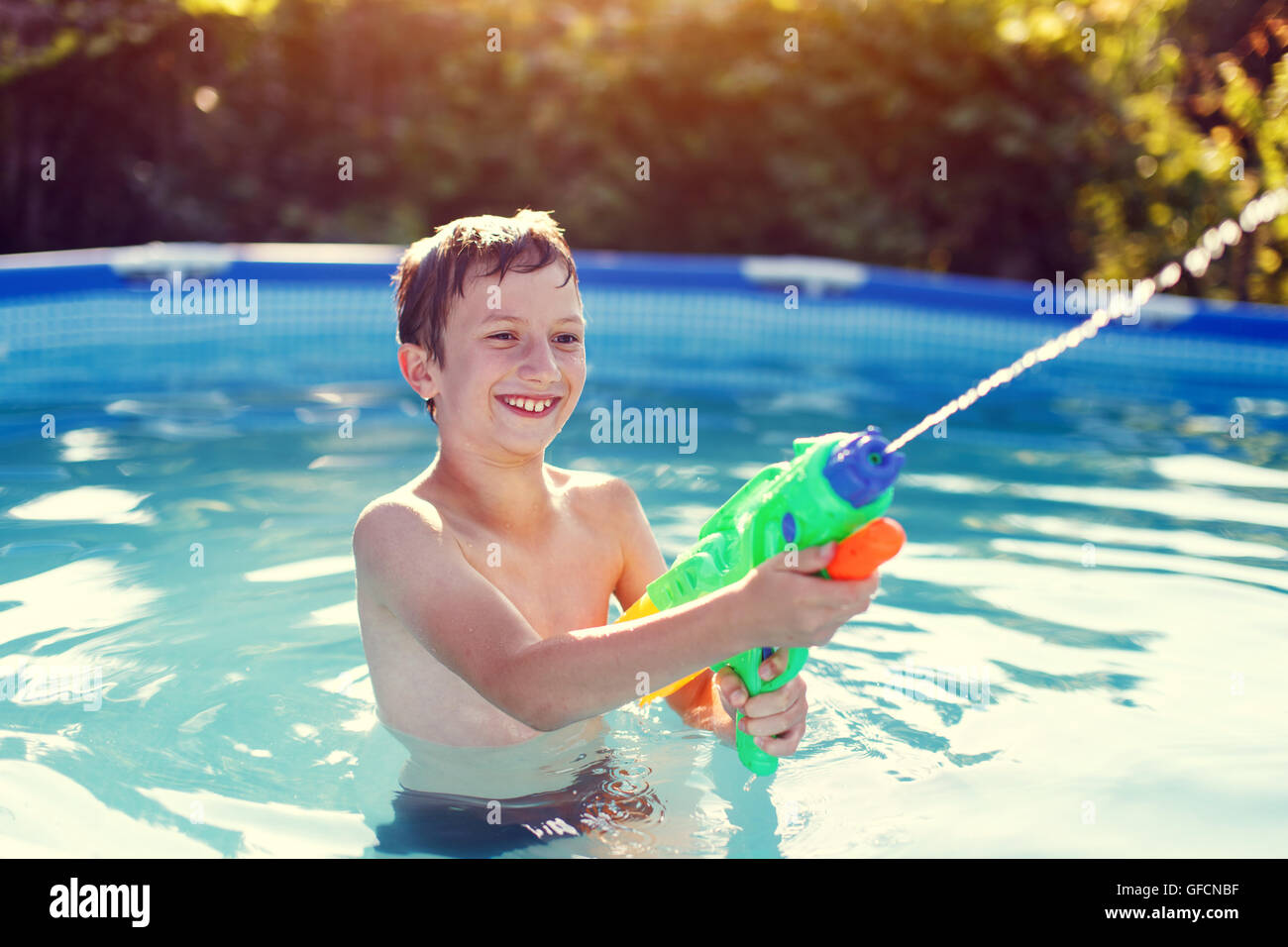 Happy little boy laugh and shoot with squirt gun in sunset - Stock Image