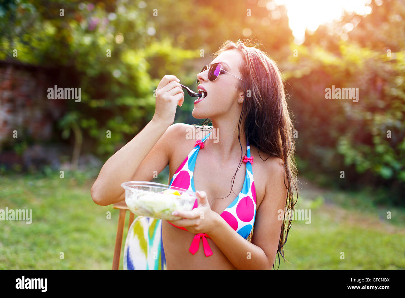 Healthy lifestyle woman in bikini eating salad outdoors in sunset. Young female eating healthy food outside in bikini - Stock Image