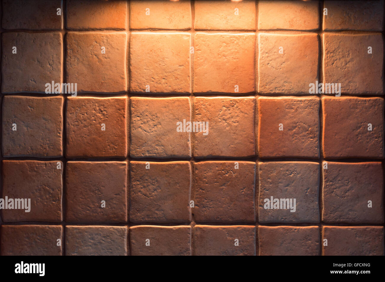 Texture of fine ceramic tiles for kitchen wall illuminated from above. Close up tiled background. - Stock Image