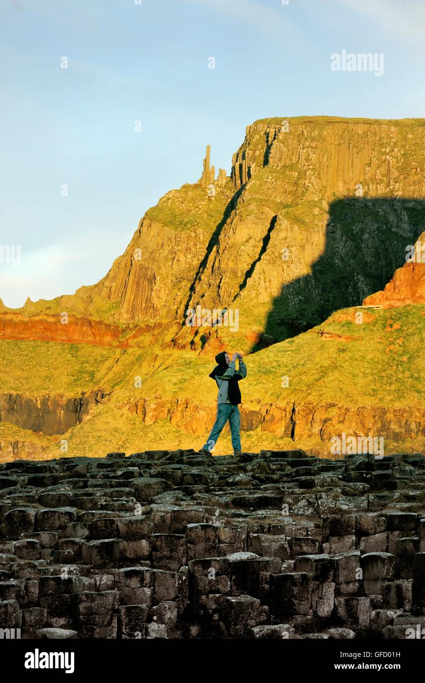 The Giants Causeway, Northern Ireland. Tourist couple take photographs on basalt rock formations known as the Grand - Stock Image