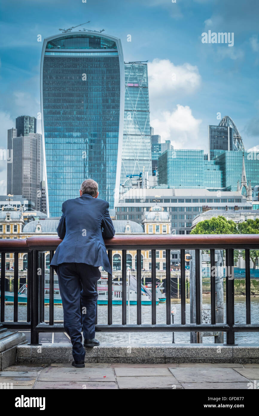 A man standing next to the river Thames on a bright sunny day with the Walkie Talkie, Cheesgrater and Tower 42 in - Stock Image