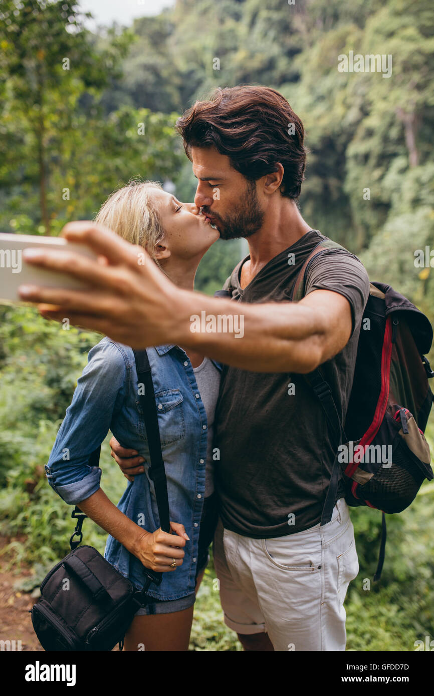 Loving young couple kissing and taking self portrait with their cell phone. Couple in love taking self picture in - Stock Image