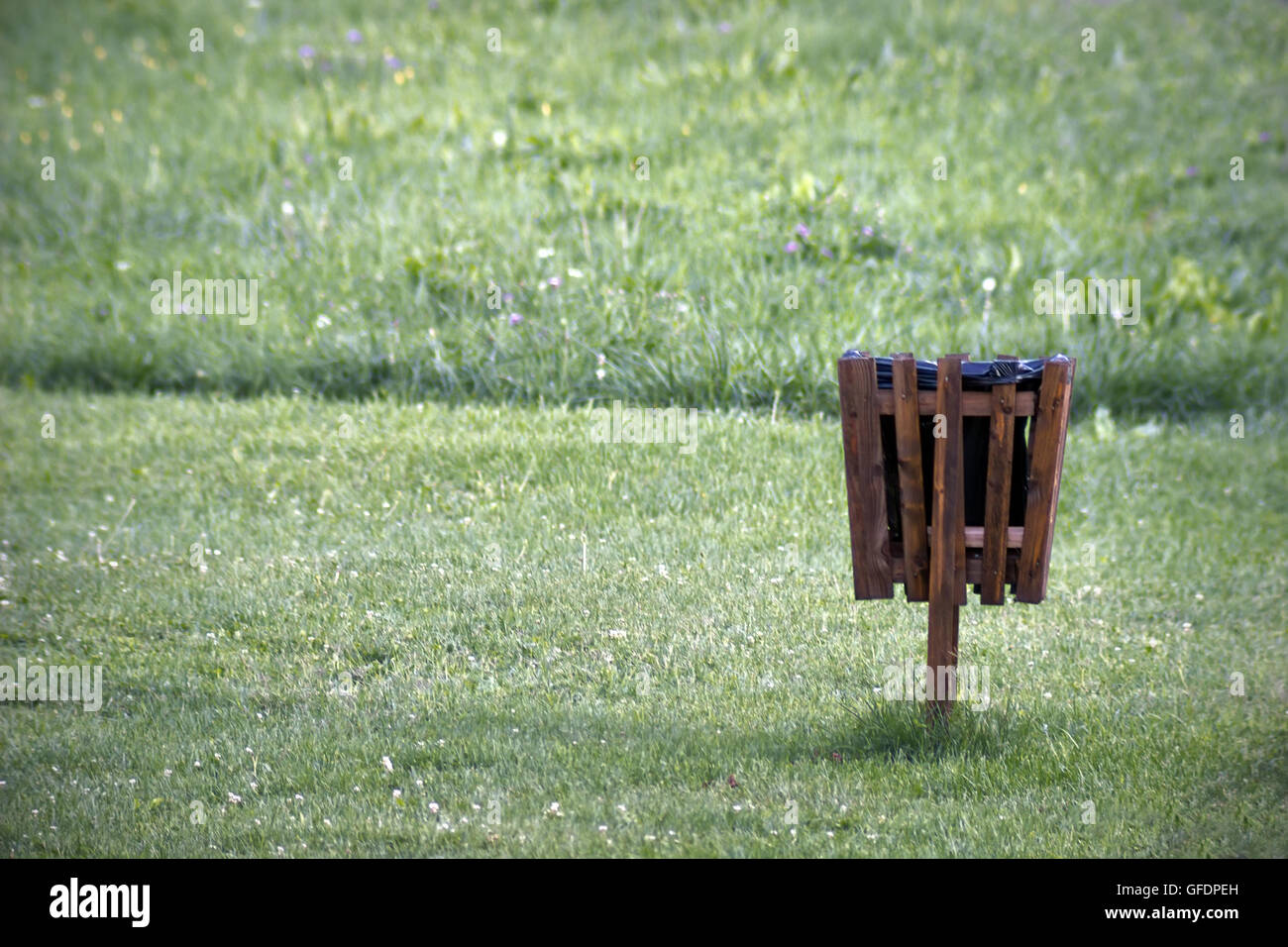 Trash can in a park. Garbage can. Wooden bin. Wooden garbage basket in park. - Stock Image
