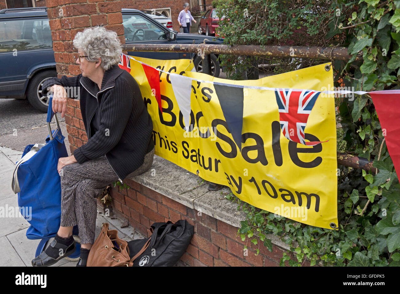 An Elderly Woman Sits On A Wall As She Waits For A Car Boot Sale To