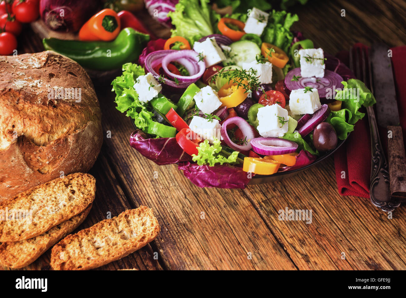 Crisp spring salad with feta cheese, full of vitamins and colors. Greec Salad on vintage table Stock Photo