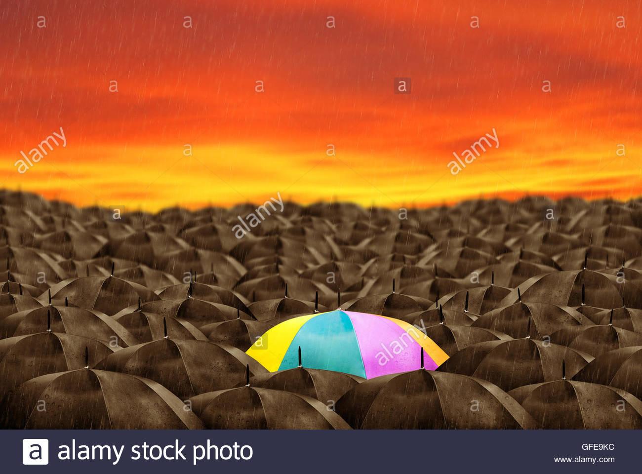 Colorful umbrella in mass of black umbrellas. - Stock Image