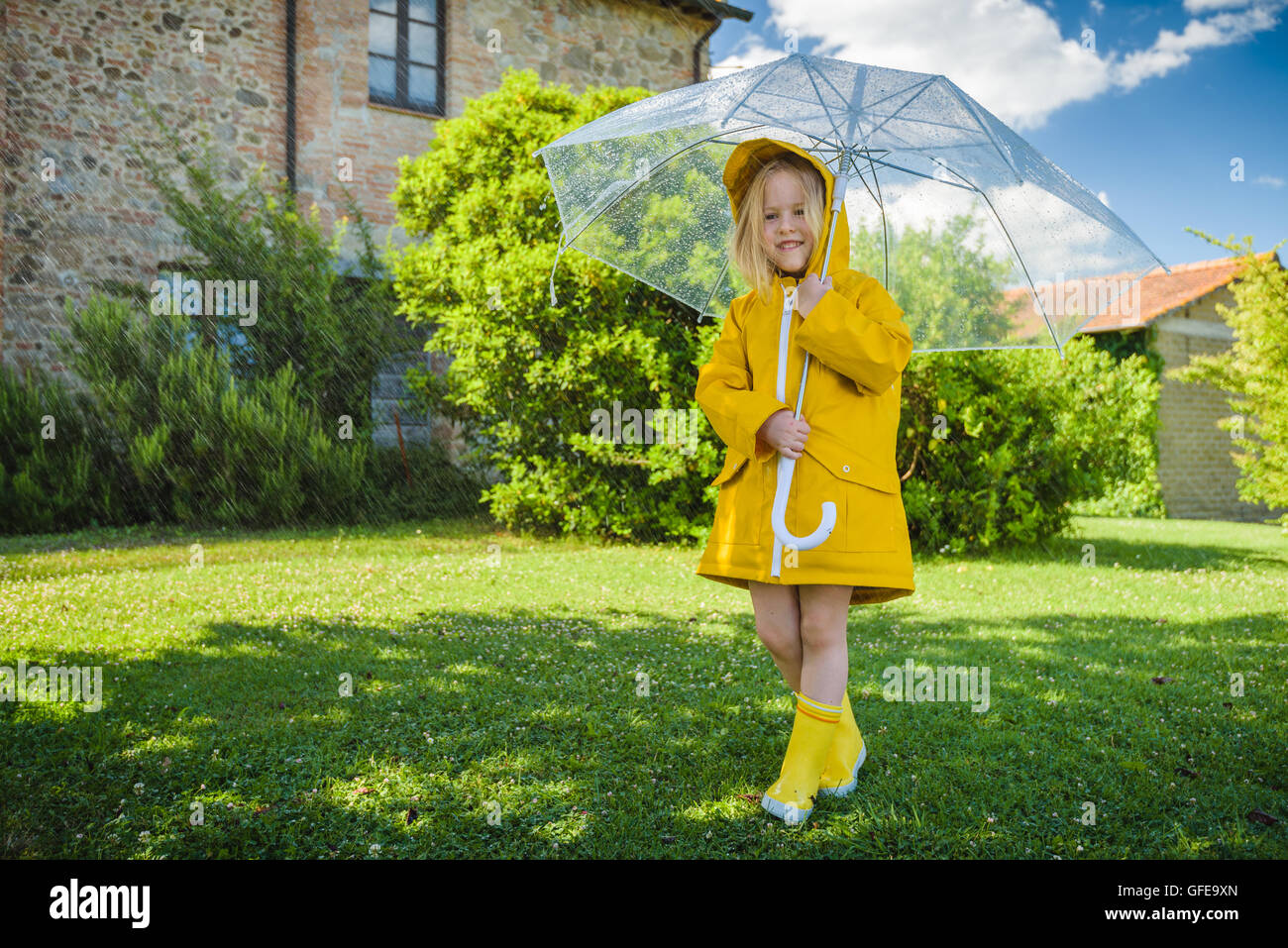 Beautiful blond girl plays with the rainy weather Stock
