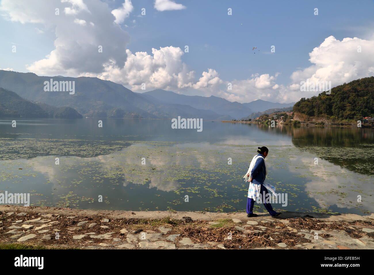 Nepalese woman walking along the shore of Phewa Lake, Pokhara, Nepal - Stock Image