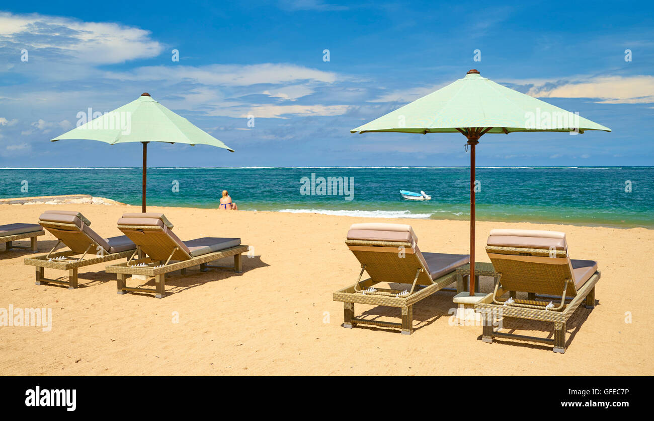 Lounge chairs with sun umbrella on the Sanur Beach, Bali, Indonesia - Stock Image