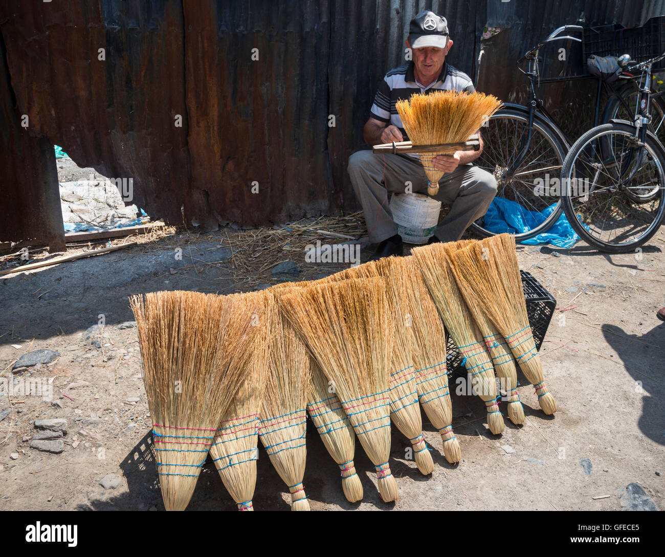 Making and selling brushes at the market in the bazaar district. Korca, South eastern Albania. - Stock Image