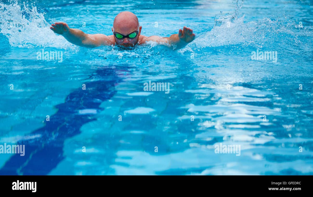 Athletic swimmer training in a swimming pool - Stock Image