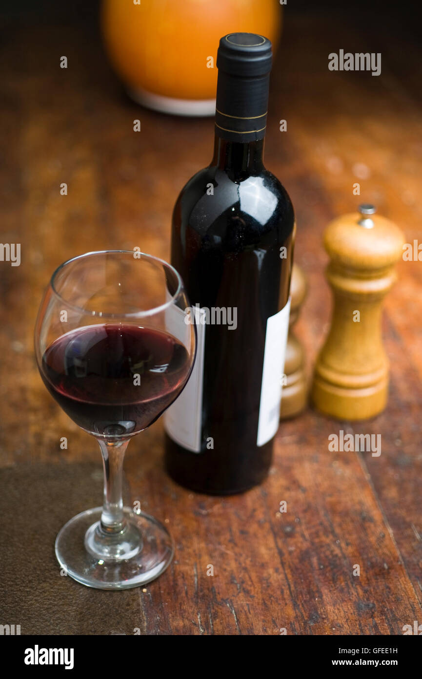 Atmospheric image of a glass and bottle of red wine The bottle has no logo or trademarks and is safe for commercial - Stock Image
