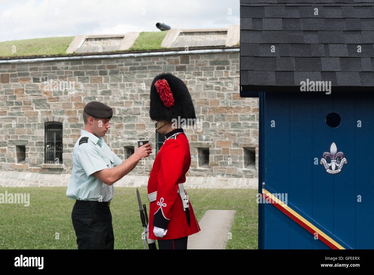 La Citadelle, Quebec, Canada - Guardsman on duty wearing a bearskin hat being given a drink through a straw on a - Stock Image
