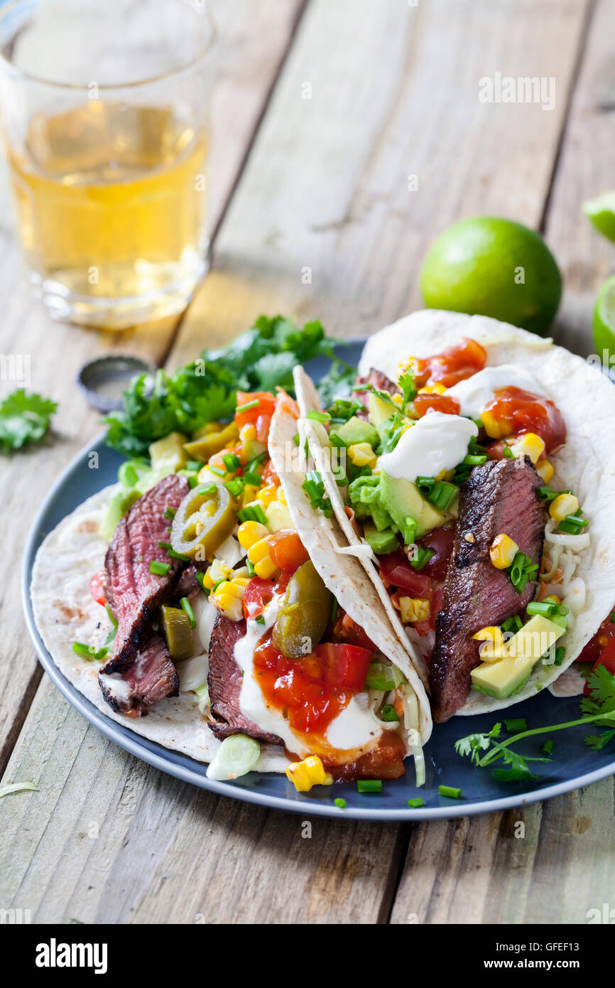 Soft tacos with fillet steak, sweetcorn, coleslaw, avocado and tomato - Stock Image