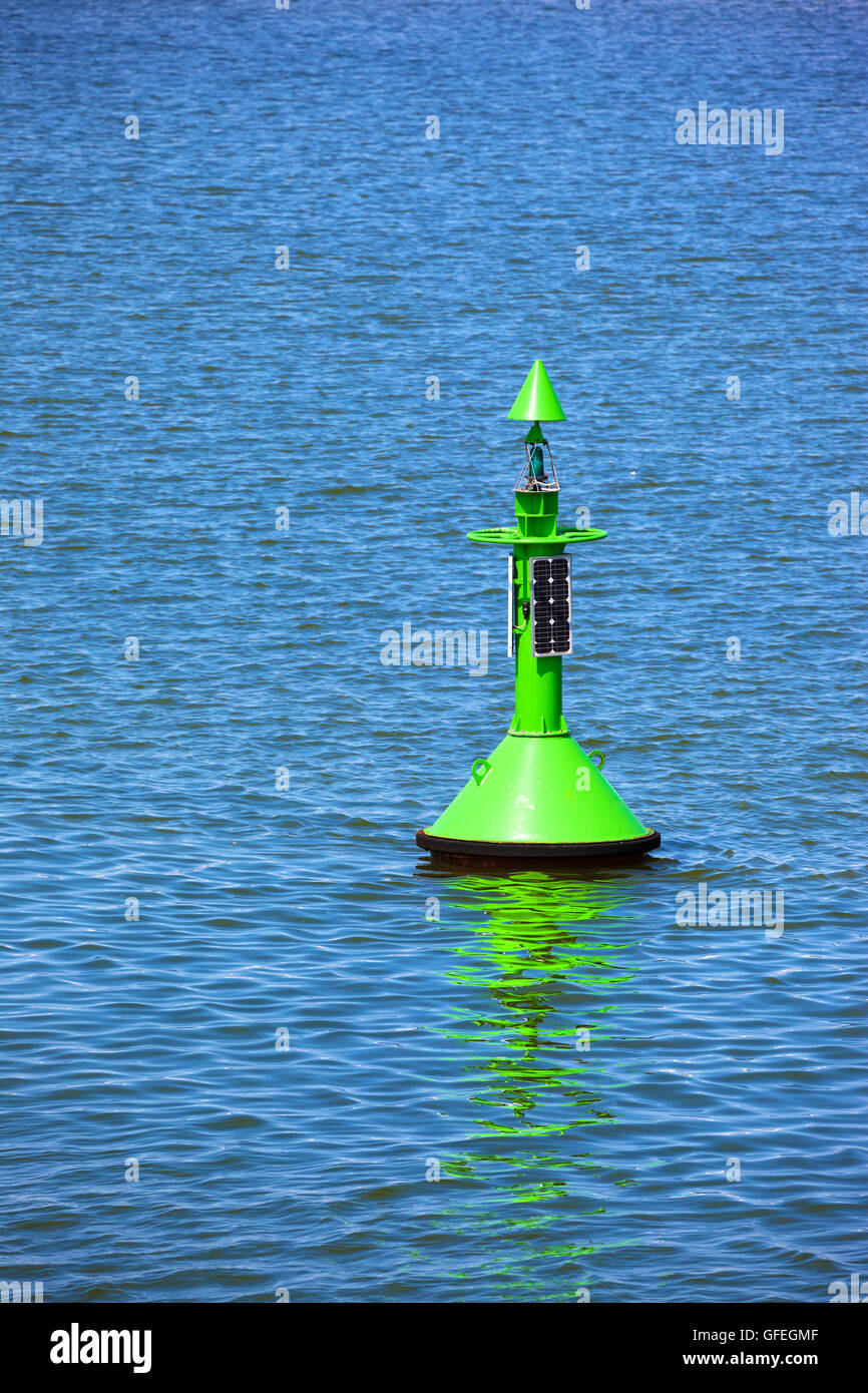 Fairway with green buoy in a sea. - Stock Image