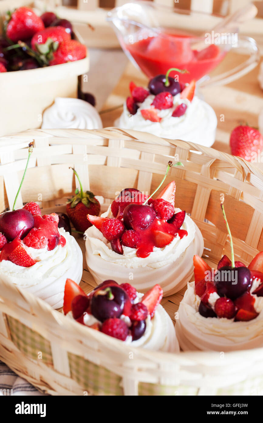 Mini Pavlova meringue cake decorated with fresh strawberry and cherry - Stock Image