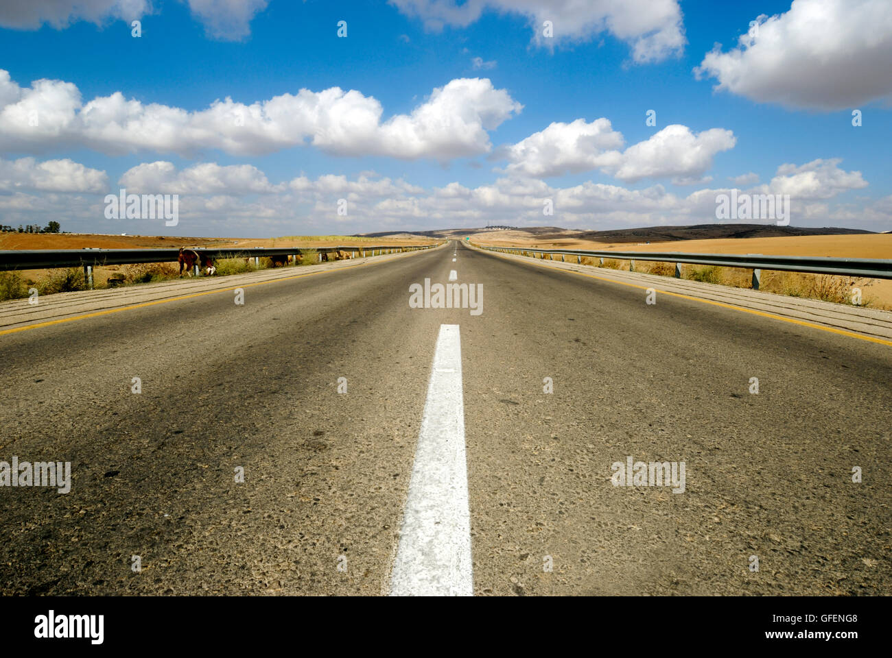 Australian, western New South Wales, Endless road to nowhere running into the horizon blue sky with clouds - Stock Image