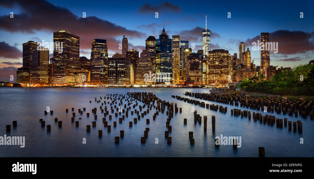Panoramic of Lower Manhattan Financial District at twilight with old pier wood pilings and World Trade Center. New - Stock Image