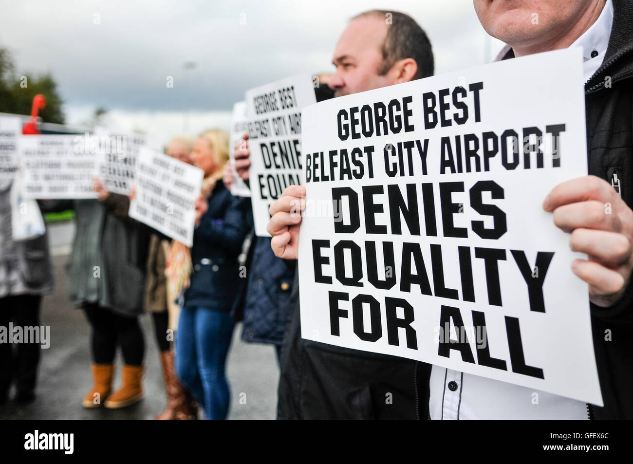 Belfast, Northern Ireland, UK. 25th Oct 2013.  Protesters hold posters saying 'George Best Belfast City Airport - Stock Image