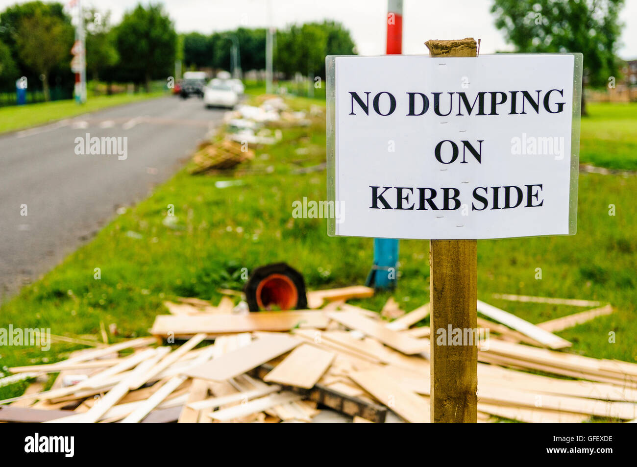 A sign on a grass verge warning people not to dump rubbish on the kerb side, with a lot of discarded wood, rubbish - Stock Image