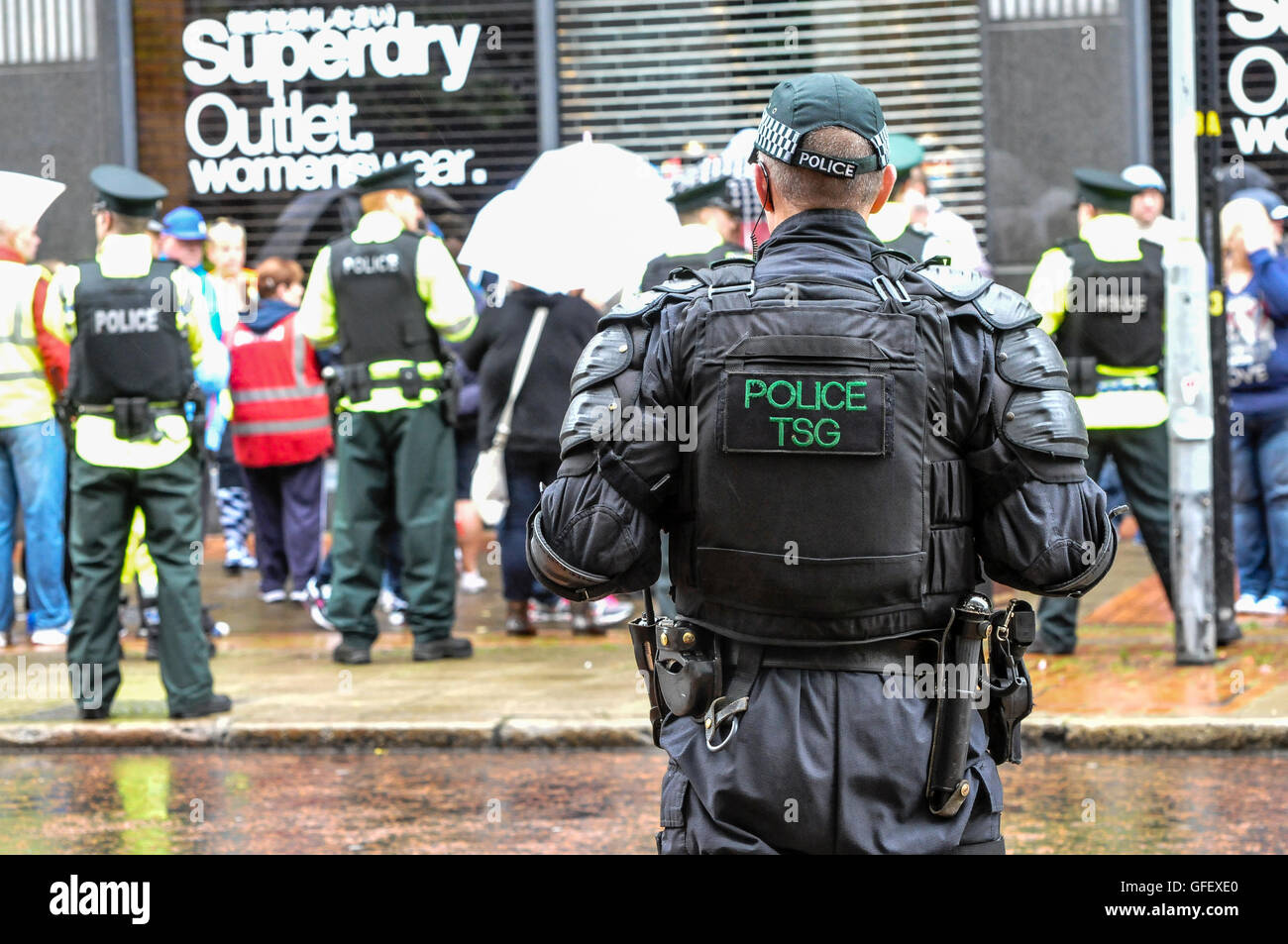 Belfast, Northern Ireland. 10 Aug 2014 - Police officers keep a crowd of people under control, while a member of - Stock Image