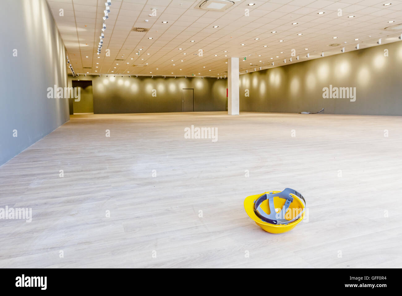 Yellow safety helmet is placed upside down on the floor of a large showroom in a modern business centre with ceiling - Stock Image